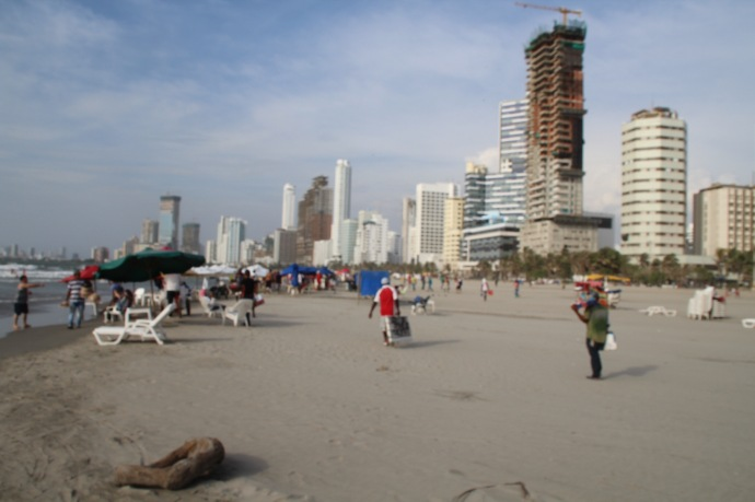 Beach by hotel with city in background