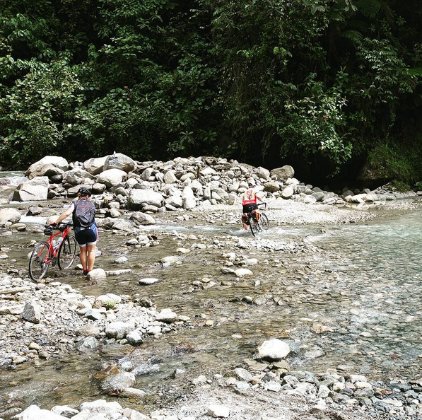 Jacqueline and Kaye navigate one of the many streams crossing the trampoline of death (Photo and caption from the TDA Global Cycling Instagram Page)