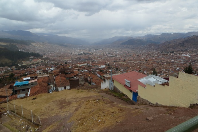 Up the hill for the final climb and down on the other side. Our first view of the main part of Cusco. The red earth, tile roofs and brown bricks make for a drab scene (Photo and caption credit: Laura and Greg's blog)