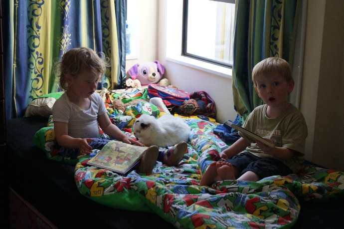 My grandchildren reading books - both so much bigger than before I left!